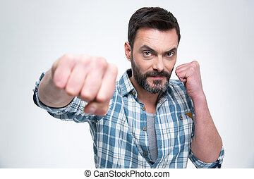 Handsome man punching with fist at camera
