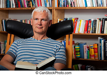 handsome man reading in a chair