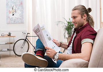 handsome man reading newspaper at home