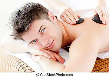 Handsome man receiving a back massage with hot stone