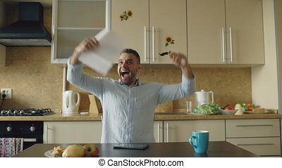 Handsome man recieve good news reading letter in the kitchen while have breakfast at home early morning