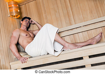 Handsome man relaxing in a sauna