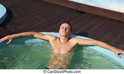 Handsome man relaxing in jacuzzi near pool outdoor
