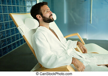 Handsome man relaxing in wellness center