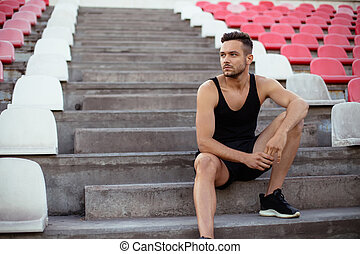 Handsome man relaxing on stadium stairs after workout