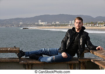 Handsome man relaxing on the pier