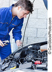 Handsome man repairing a car