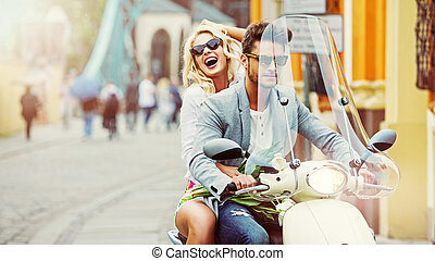 Handsome man riding a scooter with lauging girl