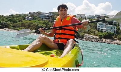 Handsome man Rowing Kayaking In a Beautiful Lagoon in the...