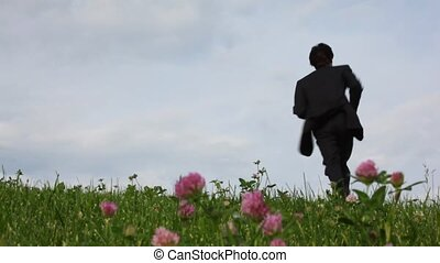 handsome man running on field of green grass and field flowers