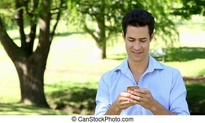 Handsome man sending a text in the park