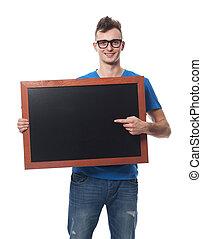 Handsome man showing on empty blackboard