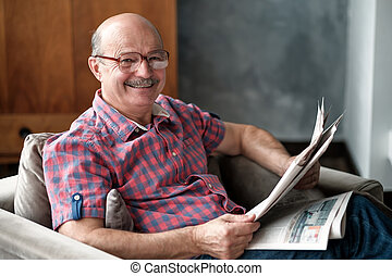 Handsome man sitting in living room, reading newspaper, smiling.