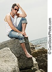 Handsome man sitting on a rock