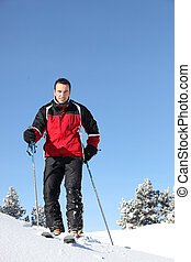 Handsome man skiing by a sunny day