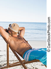 Handsome man on the beach sleeping with his hat covering his face