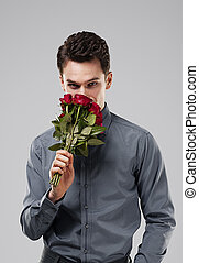 Handsome man smelling bouquet of red roses