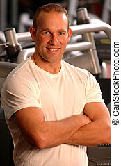 fitness center - handsome man smiling in fitness center