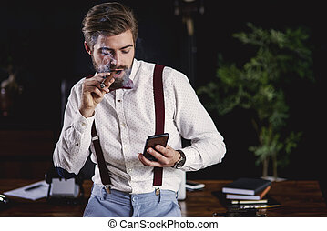 Handsome man smoking cuban cigar and reading text message
