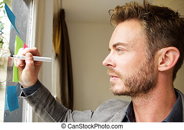 Handsome man standing in office writing on idea board