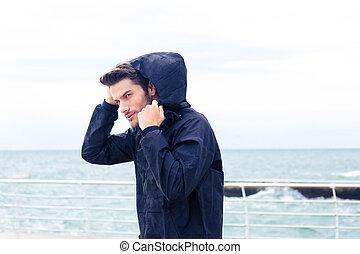 Handsome man standing near sea