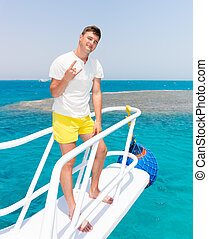 Handsome man standing on the yacht at a sunny summer day,...