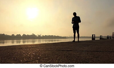 Handsome Man Stands And Looks at His Smartphone at the Dnipro at Sunset