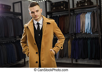 Handsome man stands in suit shop fashionable rich male dressed in expensive clothes posing indoors