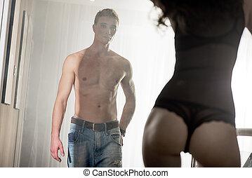 Handsome man staring at his sensual girlfriend