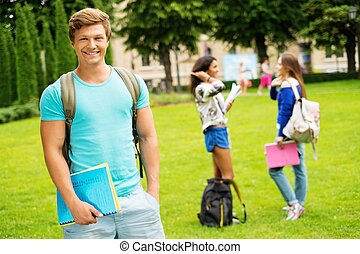 Handsome man student in a city park on summer day