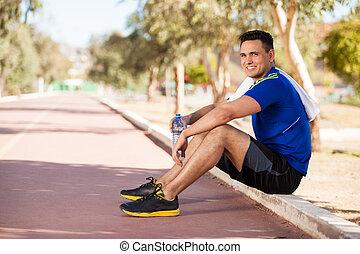 Handsome man taking a water break - Young Hispanic runner...