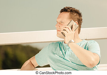 Handsome man talking on mobile phone outside