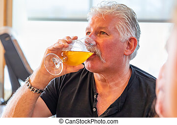 Handsome Man Tasting A Glass Of Micro Brew Beer.