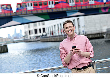 Handsome man texting on a mobile phone