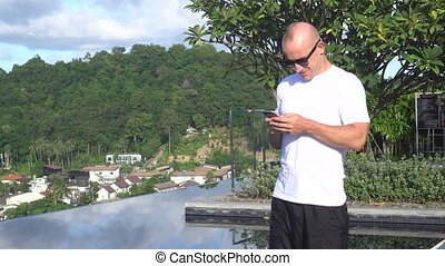 Handsome man texting on a rooftop