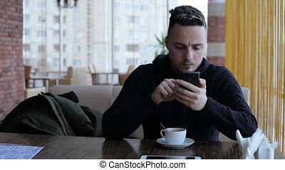 Handsome man texting, sending sms on smartphone in cafe