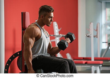 Handsome man training with dumbbells in gym