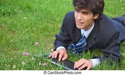 handsome man typing on keyboard lying on green grass, front view