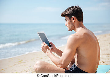 Handsome man using blank screen tablet on the beach -...