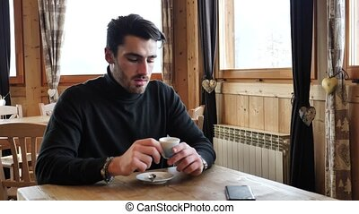 Handsome man using cellphone in cozy ski resort