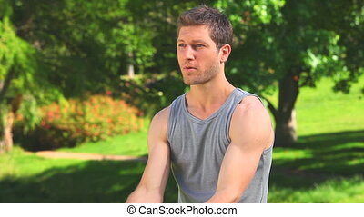 Handsome man using dumbbells outdoo