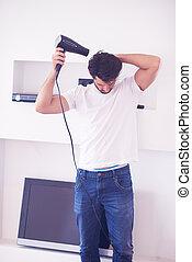 handsome man using  hairdryer