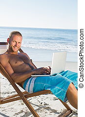 Handsome man using his laptop while sunbathing