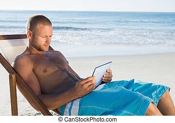 Handsome man using his tablet while sunbathing