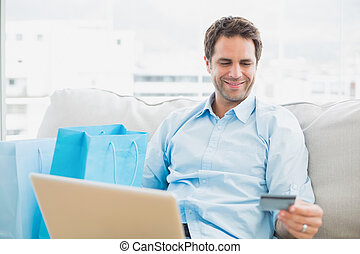 Handsome man using laptop sitting on sofa shopping online