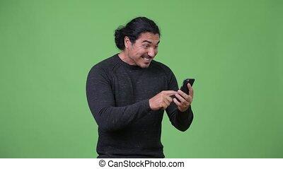 Handsome man using phone and getting good news - Studio shot...