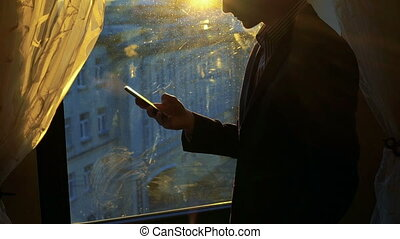 Handsome man using phone, smiling against the background of a window, curtains