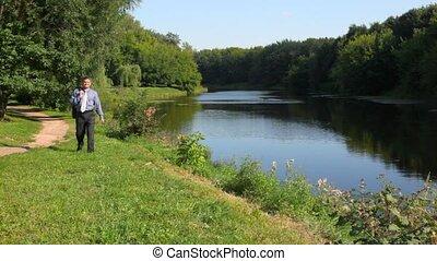 handsome man walking along bank to camera