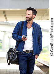 Handsome man walking on railway station