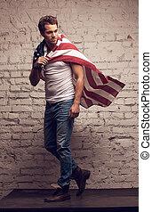 Handsome man walking using American flag like a cloak. Looking away